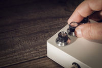 Hand sets the controls on an electric guitar pedal