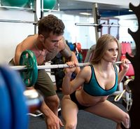 At gym. Sexy coach helps girl to do squat