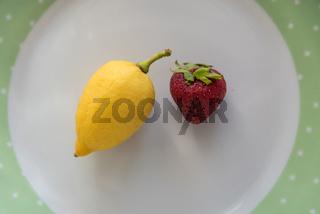 Erdbeere und Zitrone auf einem Teller - suess und sauer