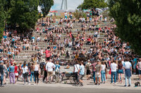 Many people in amphitheater at crowded Park (Mauerpark) wathching street performer on a sunny summer sunday in Berlin