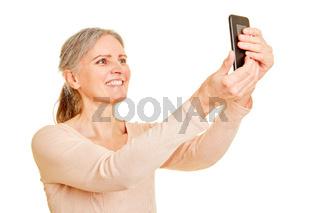 Seniorin macht Selfie mit Smartphone
