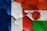 flags of France and Niger painted on cracked wall