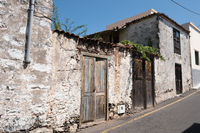 old house  with wooden door and weathered facade in rural village -