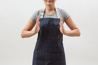 Woman chef cook in a denim apron holds your empty hands open on a white background. Mock up copy space concept .