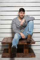 Handsome man sitting on a wooden table