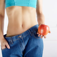 Caucasian female model in blue jeans with red apple showing her flat stomach. Healthy lifestyle and Weightloss concept.