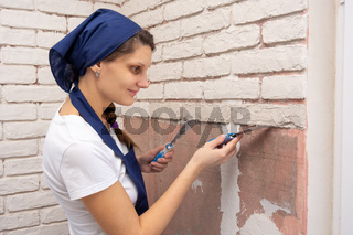 Plasterer girl forms from a plaster mass bricks on the wall