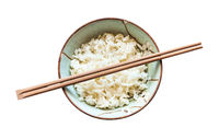 chopsticks above cup with boiled rice isolated