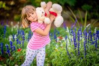 Adorable girl with a white teddy bear in a park