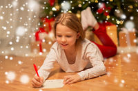 smiling girl writing christmas wish list at home