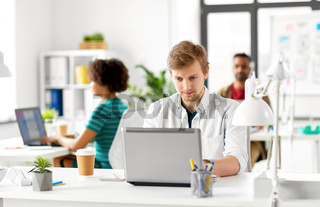 creative male office worker with laptop