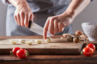 Boiled quail eggs cut female hands on a wooden board on a table with tomatoes and spinach. Step by step preparation