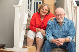Senior Couple Resting On Stairs Surrounded By Moving Boxes