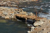 Simple timber bridge over Langtang Khola, river in Nepal. Scene near Shyaphru Besi.