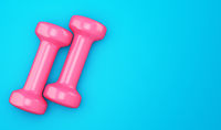 pink dumbbells isolated on blue background