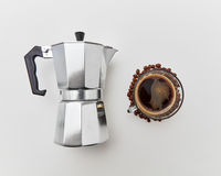 The cup of morning coffee and italian metal maker on a white background. Morning coffee concept. Top view.