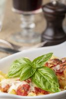 Pasta gratin auf Holz mit Basilikum