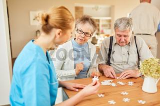 Altenpflegerin hilft Senioren beim Puzzle spielen