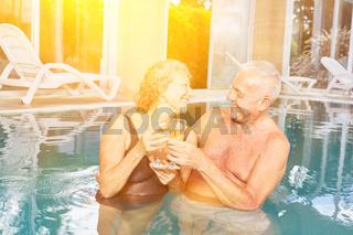 Senioren Paar beim Sekt trinken im Hotel Pool