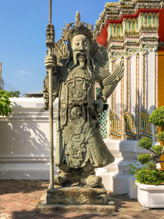 Chinese guardian figure beside a gate in the Wat Pho