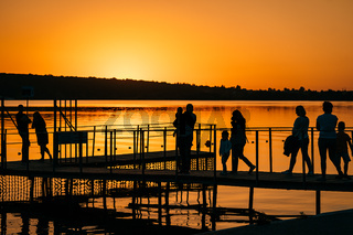 silhouettes of people at the pier, sunset