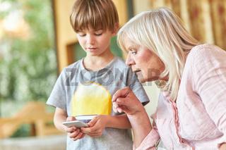 Seniorin schaut neugierig auf Smartphone von Enkel