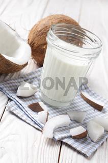 Mason jar of milk or yogurt on blue napkin on white wooden table with coconut aside