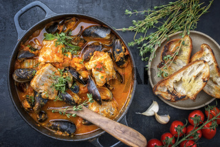 Traditional French Corsican fish stew with mussels with garlic baguette as top view in a pot