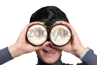 Young woman holding two half of coconut in front of eyes