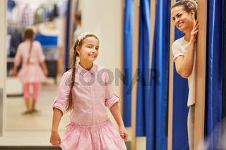 Mädchen beim Shopping probiert ein Kleid an