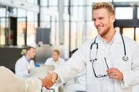 Mann als Arzt in der Ausbildung beim handshake