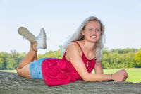 Young dutch woman lies on tree trunk in nature