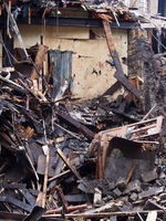black burned timbers debris and walls in a collapsed house destroyed by fire