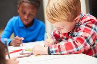 Zwei Kinder malen konzentriert Bilder