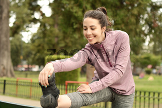 Portrair of young beautiful woman doing exercise at park