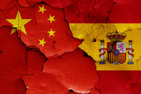 flags of China and Spain painted on cracked wall