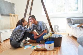 Junge Frau küsst ihren Freund bei der Renovierung