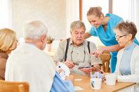 Altenpflegerin und Senioren beim Karten spielen