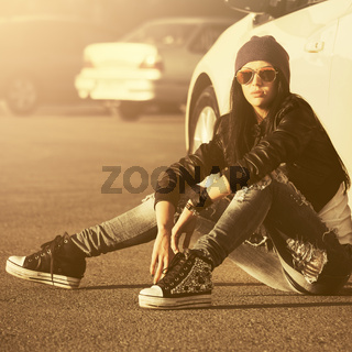 Young fashion hipster woman sitting next to her car