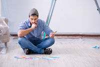 Young man contractor choosing color from rainbow