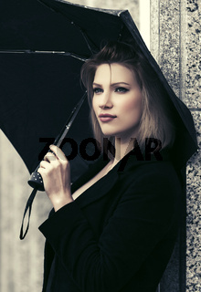 Sad young fashion woman with umbrella in city street