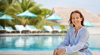 happy woman over swimming pool of touristic resort