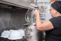 woman employee loading casseroles into an industrial dishwasher in the restaurant.