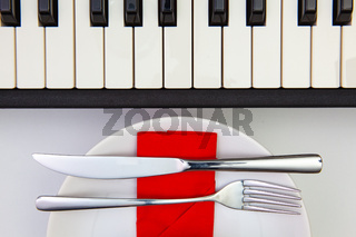 White plate and piano keys on the white  wooden table.