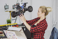 Woman examining radio-controlled car in workshop