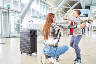 Sohn begrüßt seine Mutter im Flughafen Terminal