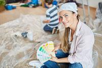 Frau mit Muster für Wandfarbe beim Renovieren
