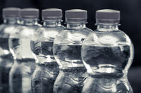 Row of water bottles, bubbling spa red, recycling environment concept black and wite