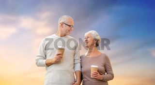 happy senior couple with coffee over evening sky