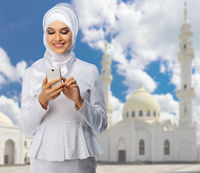 Young muslim woman on white mosque background